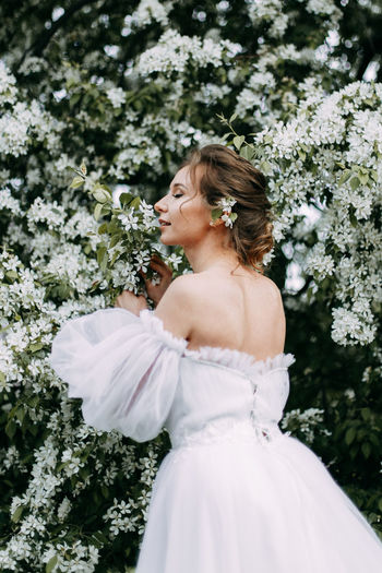 A beautiful young woman bride in a wedding dress walks alone in a blooming spring outdoor park