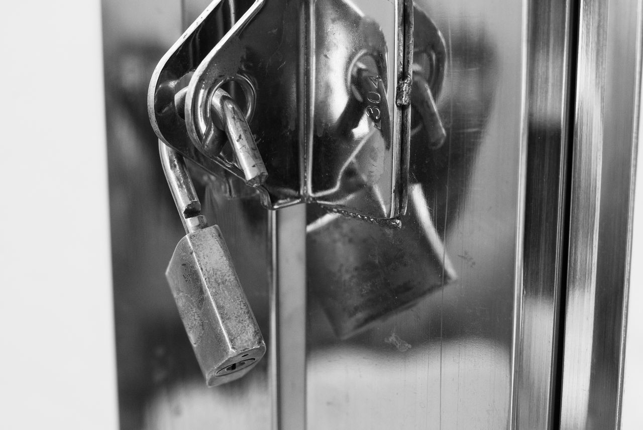 close-up, indoors, focus on foreground, no people, glass - material, hanging, metal, window, reflection, transparent, lock, mirror, selective focus, looking, day, representation, still life, human representation