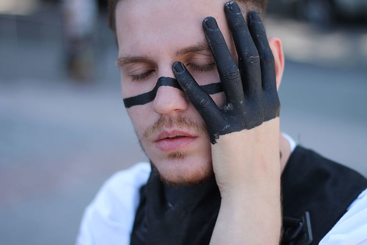 Close-up of man with eyes closed and face paint standing outdoors