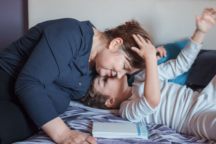 Grandson Kissing Grandmother On Bed At Home