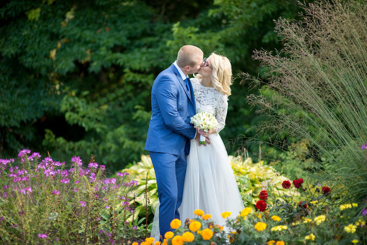 Bridal couple kissing while standing amidst flowers blooming at park