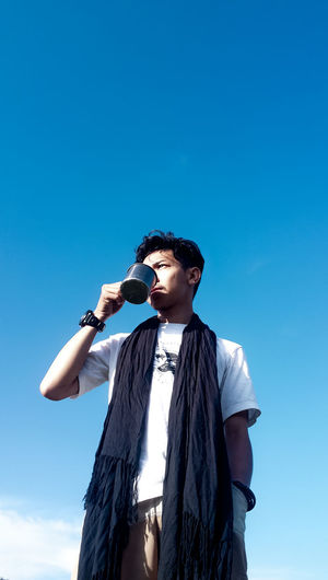 Low angle view of thoughtful young man drinking coffee standing against blue sky