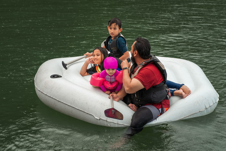 Man with children floating on lake