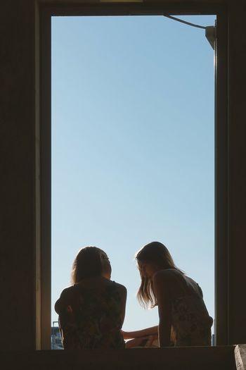 Sisters sitting at doorway