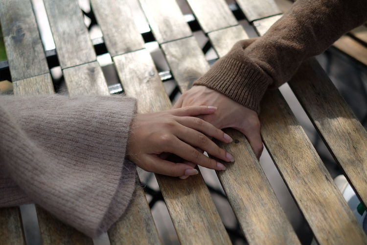 Close-up of couple holding hands on table