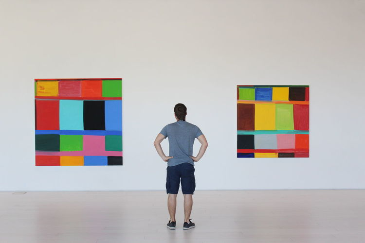Rear view of man standing against multi colored wall