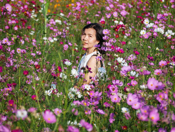 Portrait of smiling woman with pink flowers in bloom