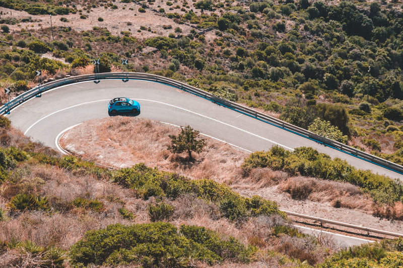 Little blue car in the road. Transportation Mode Of Transportation High Angle View Plant Tree Road Nature Motor Vehicle Day Car Land Vehicle Environment Land Travel Landscape No People Beauty In Nature Outdoors Motion Mountain Blue Car Mini Car Fiat500 Desert Landscape Mediterranean