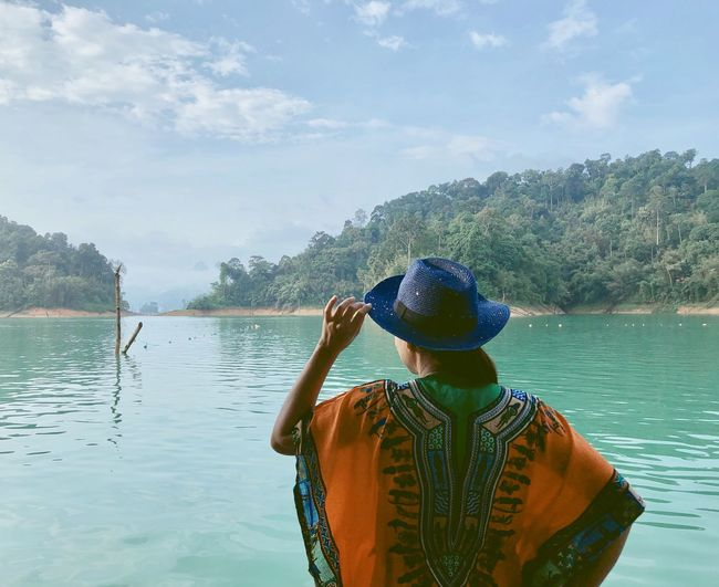Rear View Water Leisure Activity Real People One Person Hat Lifestyles Day Men Waist Up Lake Cloud - Sky Standing Nature Casual Clothing Sky Clothing Tree Outdoors Looking At View