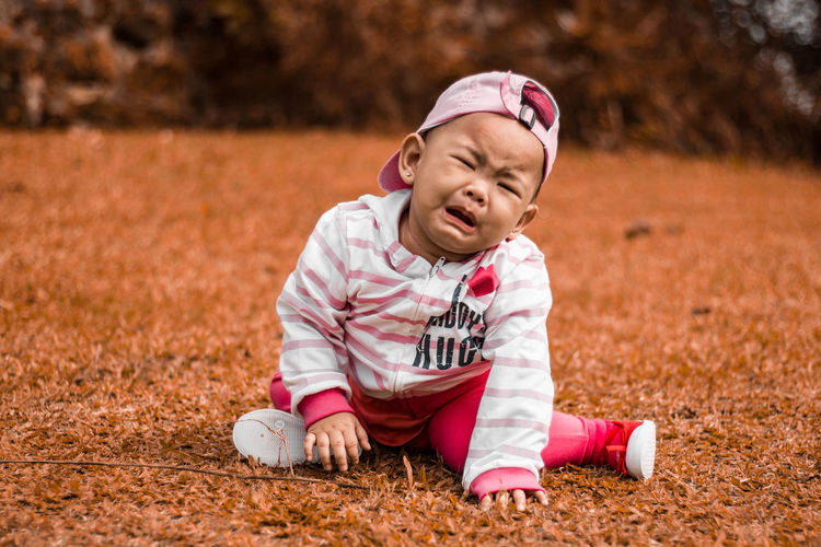 Close-up of baby girl crying on field