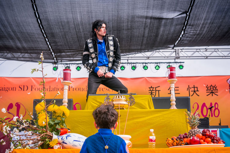 A Michael Jackson impersonator performs at the San Diego Lunar New Year Tết Festival 2018 as a little boy close to the stage watches just below a table of offerings honoring Vietnamese ancestors. The annual event is produced by the Little Saigon Foundation of San Diego (Photo taken Feb. 10, 2018 on the festival grounds of the SDCCU Stadium) America Diversity America Multicultural America Pop America Pop Diverse Dance Diversity Honoring Michael Jackson Michael Jackson Impersonator Michael Jackson Boy Michael Jackson Impersonator Boy Vietnamese Vietnamese American America Culture America Pop Culture Arts Culture Arts Culture And Entertainment Culture And Tradition Culture Dance Music Impersonator Michael Jackson Son Multicultural Music Culture Performance Tribute