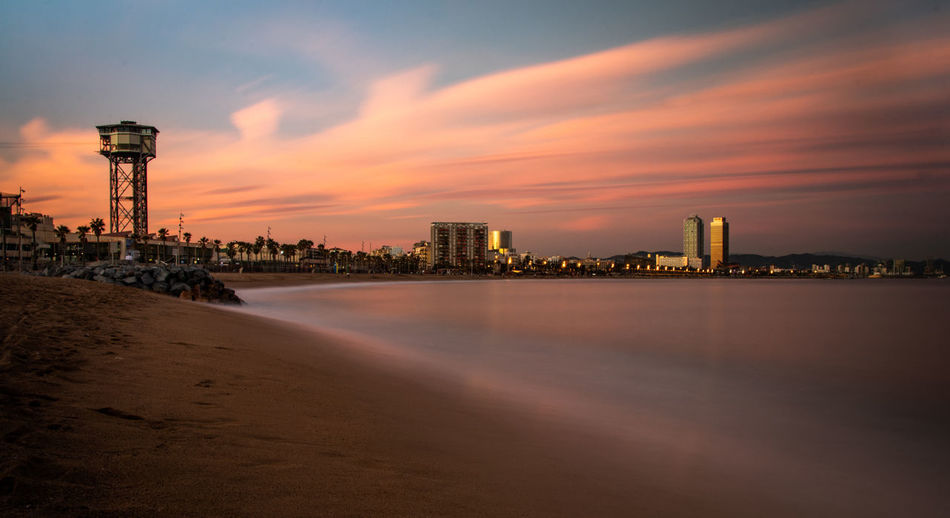 Sky Architecture Sunset Built Structure Building Exterior Cloud - Sky Water Building Nature Waterfront Land No People Tower City Beach Sea Orange Color Tall - High Outdoors Office Building Exterior Skyscraper Cityscape Barcelona Barceloneta Barceloneta Beach Longexporure Long Exposure Playa Calm Place Calm Peace Mer Market Sand Sable Arena