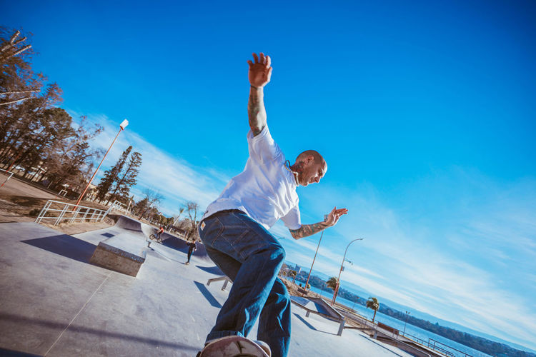 Man Skateboarding Against Blue Sky During Sunny Day