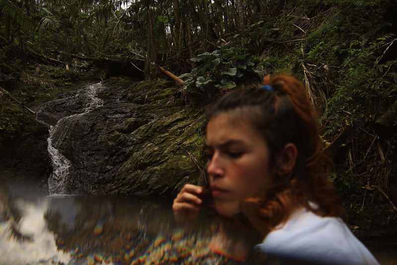 Double exposure of woman and stream at forest