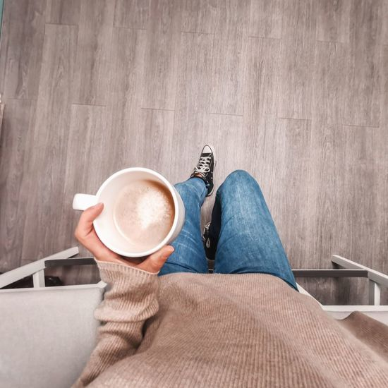 Low section of woman with coffee cup