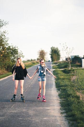 Friends roller skating on road