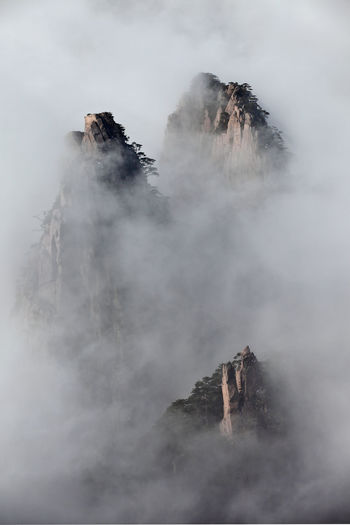 Scenic view of rocky mountains during foggy weather