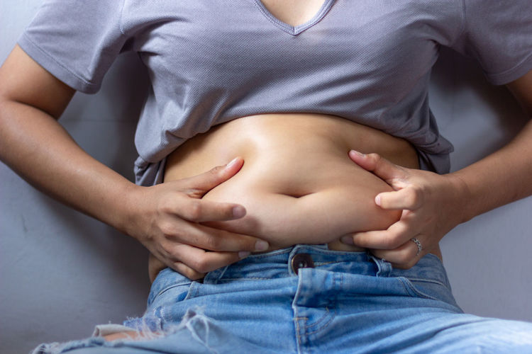 Midsection of man touching belly while sitting against wall