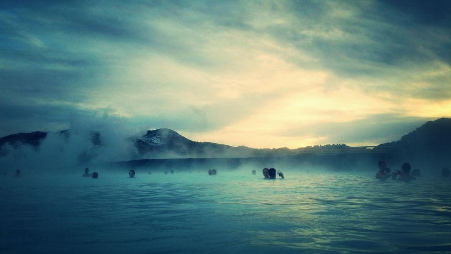 People at blue lagoon against sky