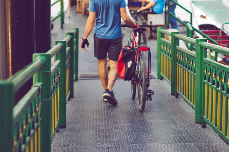 Low section of man with bicycle walking on footbridge