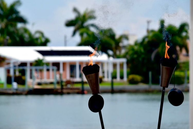 Burning Torch Close-up Flaming Focus On Foreground Hanging No People Torches Torchlight Tree Vacations Water Waterfront Waterscape Waterscape Photography