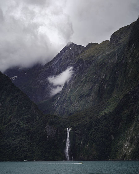 Scenic view of waterfalls through the mountains against a cloudy sky