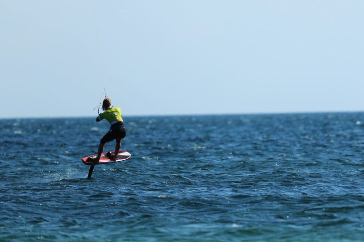 Woman kiteboarding in sea against clear sky