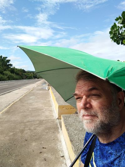 Close-up of mature man standing with umbrella at roadside