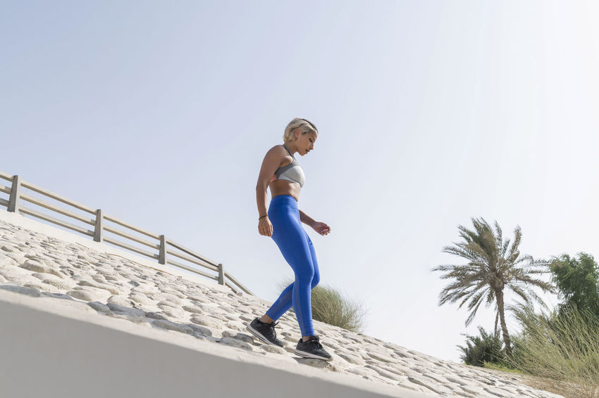 Middle Eastern Girl with short braided hair running down hill on a urban side street wearing blue and gray fitness outfit on a hot bright sunny day. Exercising Jumping Off Rocks Sitting Bright Day Casual Clothing Clear Sky Clothing Copy Space Day Dusty Fitness Model Full Length Hot Day ☀ Land Leisure Activity Lifestyles Low Angle View Middle Eastern Woman Nature One Person Real People Sky Sport Sports Clothing Stretching Sunlight Tree Young Adult