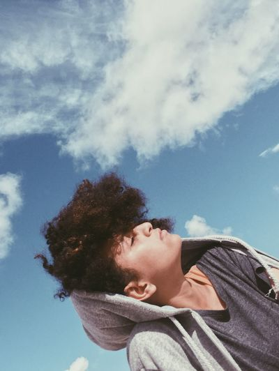 Low angle view of young woman with eyes closed against blue sky during sunny day