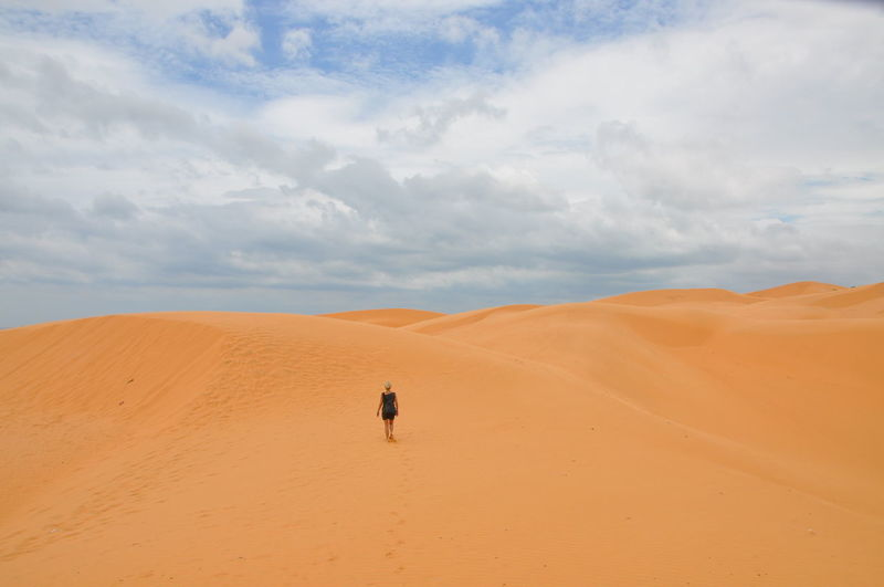 Scenic View Of Woman Walking In Desert Against Sky