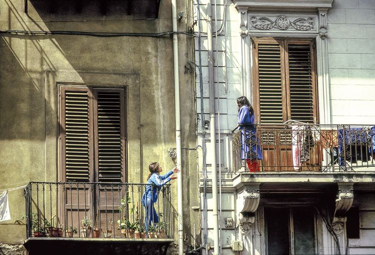 Low Angle View Of Women Talking While Standing In House Balcony