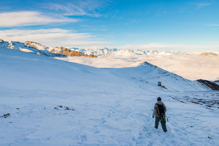 Rear view of woman hiking on snowcapped mountain