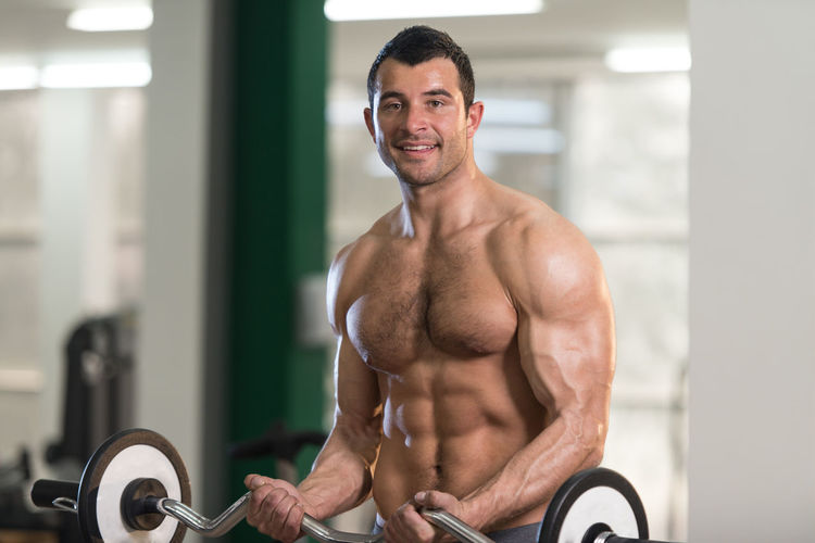 Portrait of happy shirtless young man exercising in gym