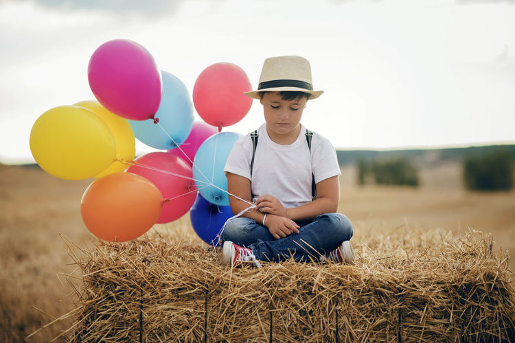 Alone Cry Dream Field Freedom Grass Holidays Independence Loneliness Pensive Travel Balloon Boy Child Childhood Crying Child Field Fragility Lifestyles One Person Outdoors Portrait Sad Sadness Sitting