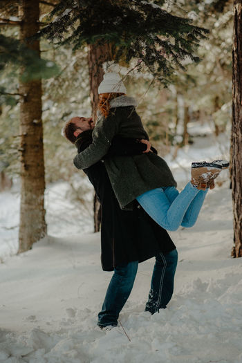 Couple embracing while standing on snow covered land