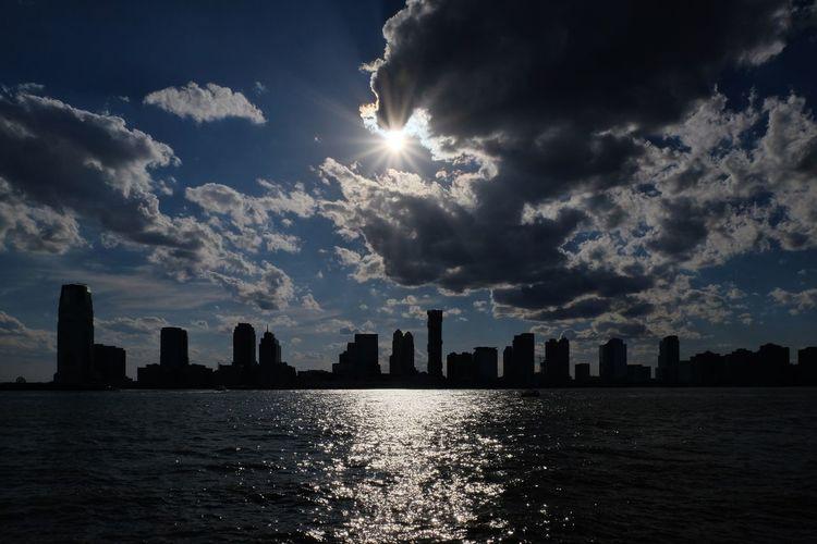 City skyline by river against dramatic sky