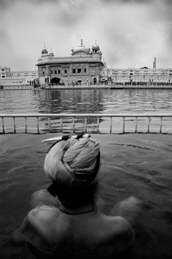 Rear view of sikh man bathing at golden temple