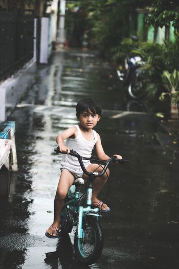 Boy riding bicycle on wet street