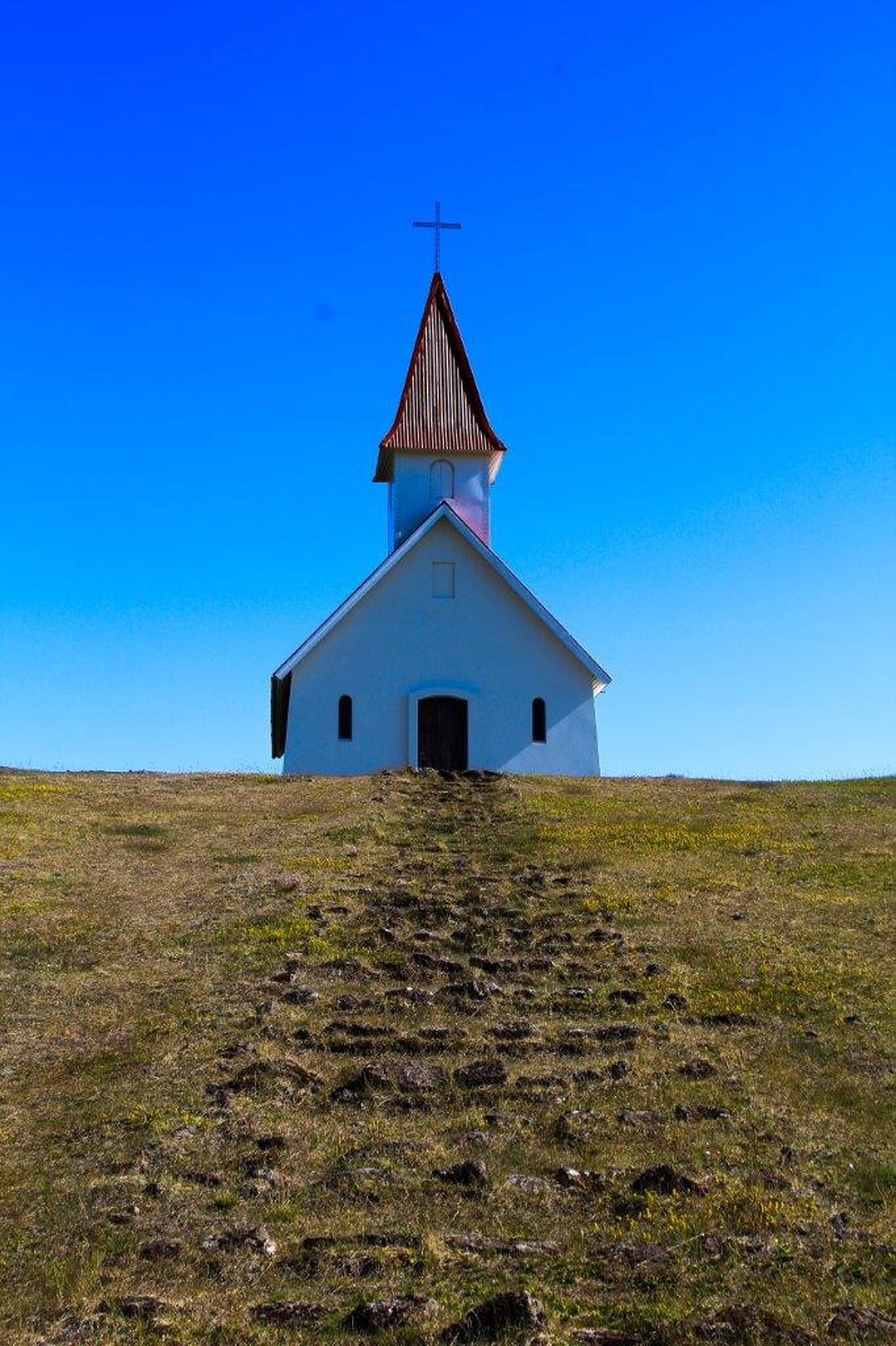 architecture, building exterior, built structure, religion, place of worship, church, spirituality, blue, clear sky, cross, copy space, house, low angle view, sky, sunlight, day, outdoors, tower