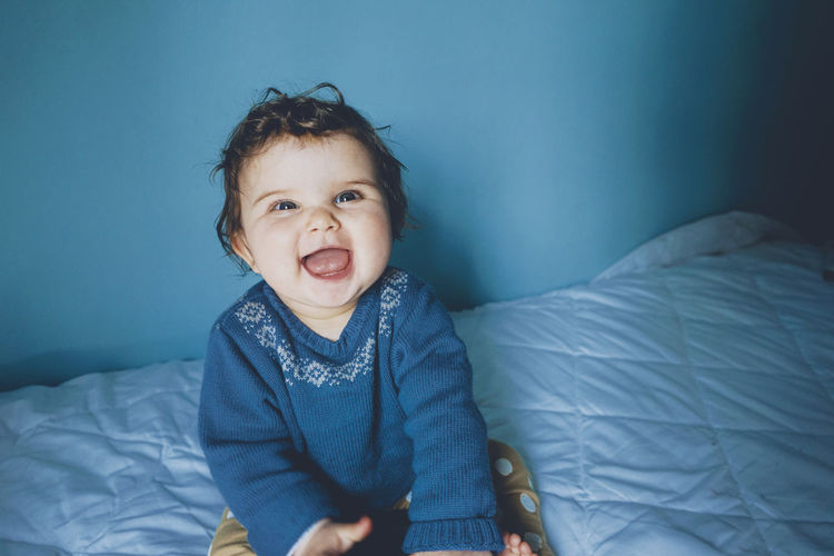 Portrait of smiling boy on bed at home
