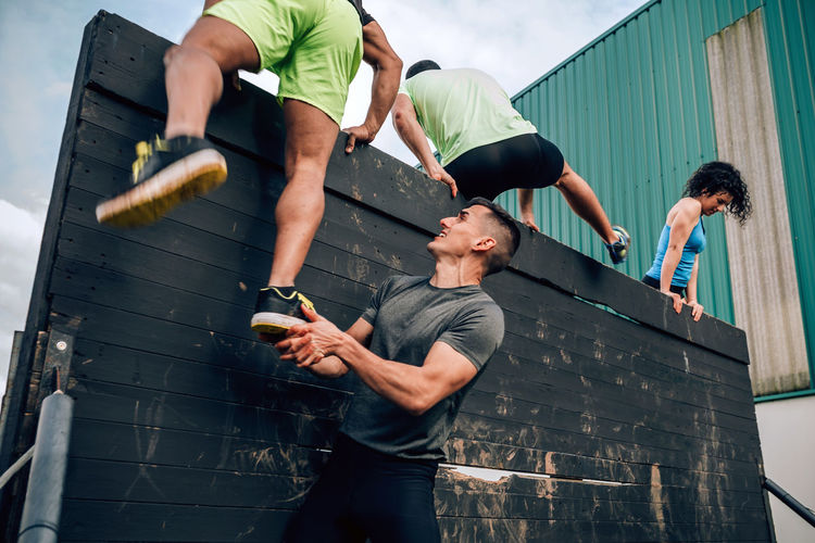 Young man assisting friend while climbing wooden wall