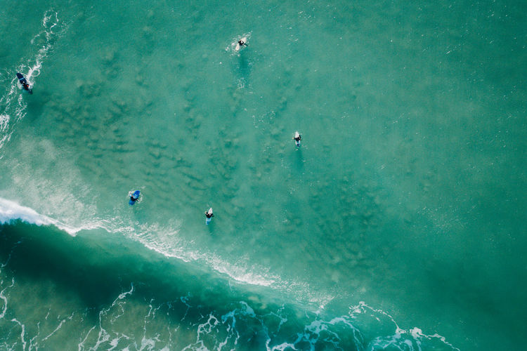 High angle view of people with surfboard in sea