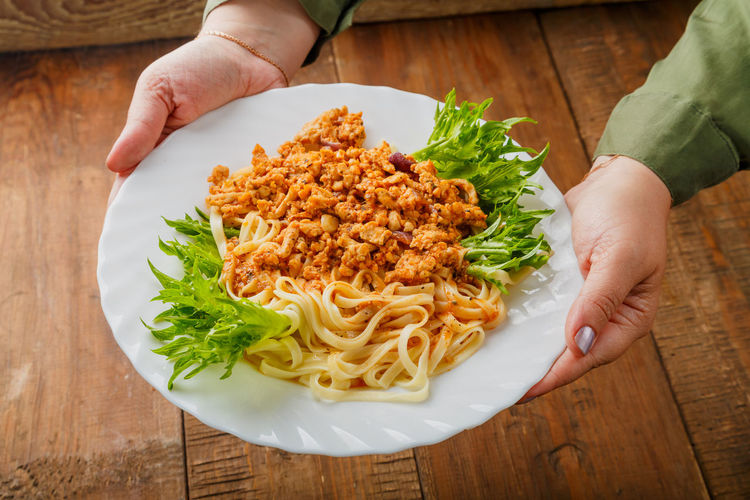 A plate of pasta in bolognese sauce in female hands. horizontal photo
