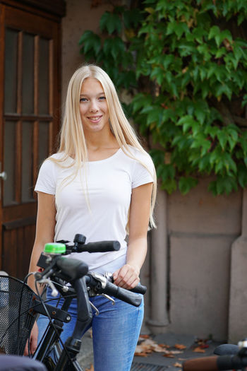 Blond Hair One Person Long Hair Beautiful Woman Young Adult Teenager Teen Teenage Girls Female Woman Girl Young Women Blonde Outdoors Real People People person Portrait Smiling Casual Clothing Three Quarter Length Happiness Bicycle Looking At Camera Day Bike Cycling Standing Door