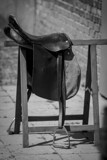 Close-up of saddle on metal rack