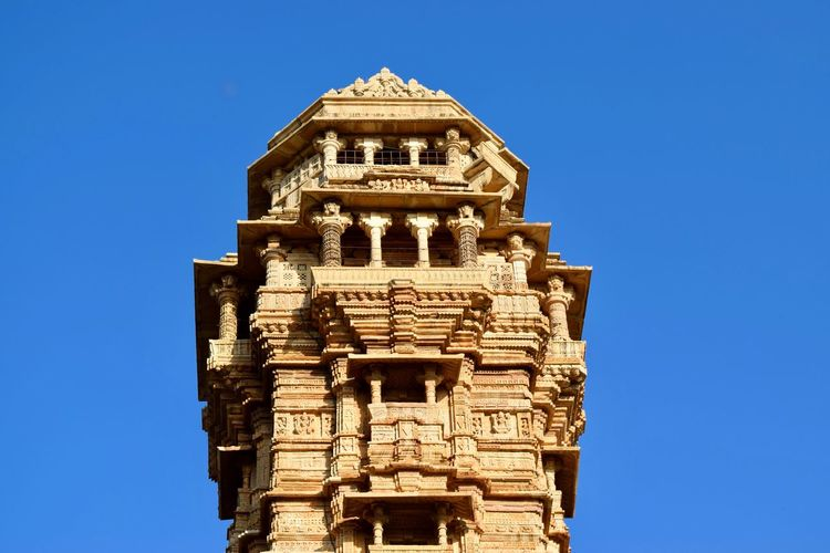 Low angle view of vijaya stambha against clear blue sky