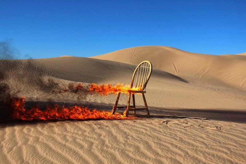 Burning Chair In Desert Against Clear Blue Sky