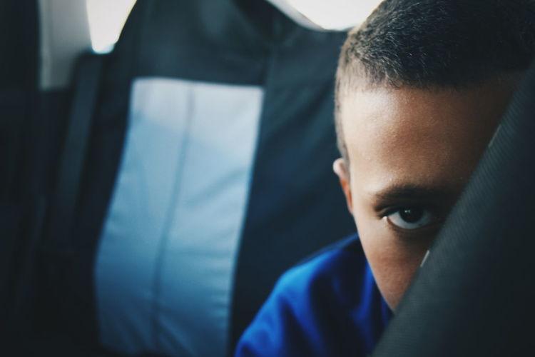 Portrait of boy hiding behind fabric