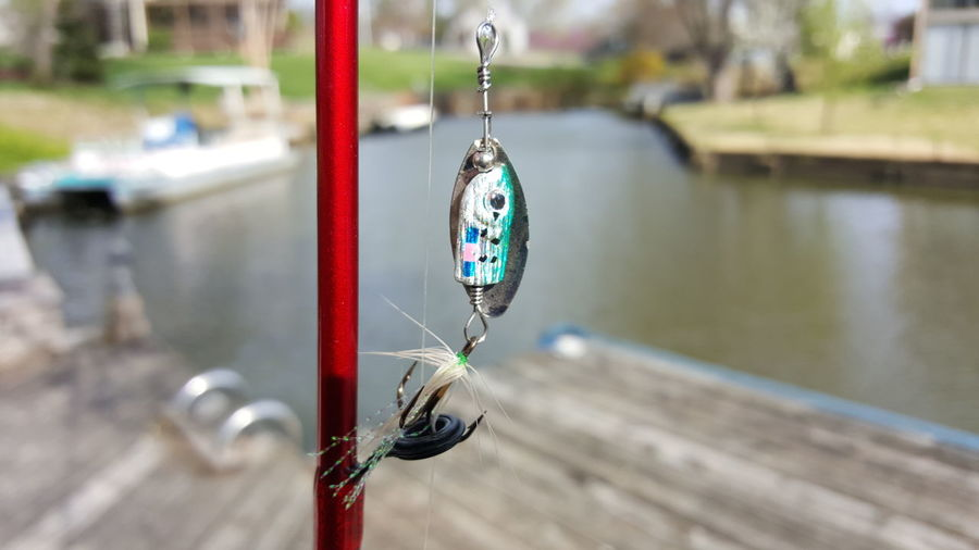 Close-up of fishing pole against the lake